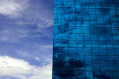 Blue Building. A modern blue glass building reflecting a clouded sky Royalty Free Stock Images