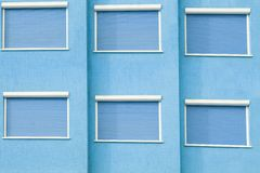 Blue Building Facade with Six Closed Windows Shutters Stock Photos
