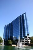 Blue Building on Lake. Blue Office tower on lake with fountain Stock Photography