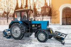 Blue bulldozer cleans the streets after a heavy natural snowfall. Getting ready for Christmas. Sunny frosty day. Close-up. The horizontal frame Stock Photography