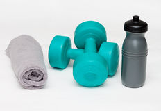 Blue bumbbells with gray bottle and towel on white Stock Images
