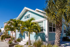 Blue Bungalow and Palm Trees Stock Photos