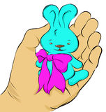 Blue Bunny on palm. Blue bunny with a pink bow on the palm Stock Photo