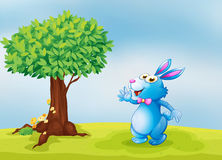 A blue bunny beside a tree Stock Photography