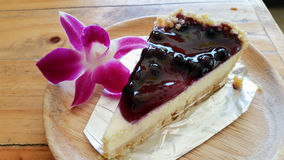 Blue bury cheesecake with Orchid flower on wooden plate Royalty Free Stock Images