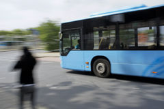 Blue bus driving by Stock Photo