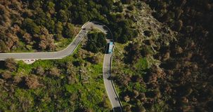 Blue bus turns left on a mountain road aerial view. Dangerous narrow forest driveway. Traffic road safety. Travel 4K. Blue bus turns left on a mountain road stock video footage