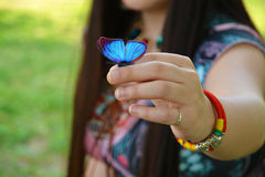 Girl holding blue butterfly on her hand Stock Images
