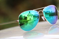 Beautifull view through colored glasses and aimed on church. Blue butterfly in green nature Royalty Free Stock Images