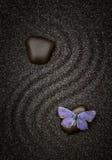 Blue butterfly on a zen black stone Royalty Free Stock Photography
