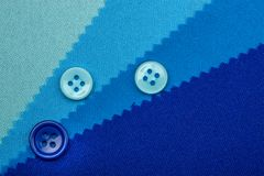 Blue button and samples of fabric texture detail stock image