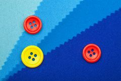 Blue button and samples of fabric texture detail Royalty Free Stock Photos