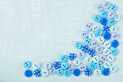 Blue buttons on linen - sewing background Royalty Free Stock Photo