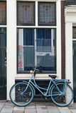 Blue bycicle in front of window. On a street in Amsterdam Royalty Free Stock Images