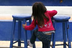 Blue Cafe Series - Little girl. Little girl getting up on the high stool royalty free stock image