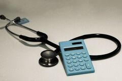 Blue calculator and black stethoscope, Medical financial backgrounds concepts