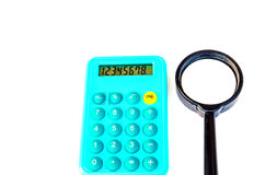 Blue calculator and magnifying glass in black Royalty Free Stock Photo