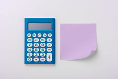 Blue calculator with a paper sticker Stock Photos