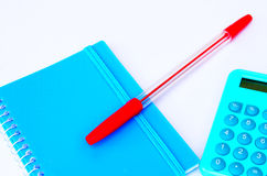 Blue calculator, red pen and blue notebook on a white background. Blue pen and notebook on a white background Royalty Free Stock Image