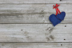 Blue calico hearts hanging on wood background Royalty Free Stock Photos