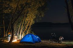 Blue Camping Tent Illuminated Inside. Night Hours Campsite. Recreation. Motorcycle traveler, tourist bikers. lake and stars. take royalty free stock photo