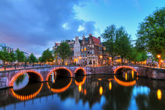 Blue canal Amsterdam. Beautiful cityscape of the famous canals of Amsterdam, the Netherlands, at night with bridges at the Emperor`s canal keizersgracht and Stock Image