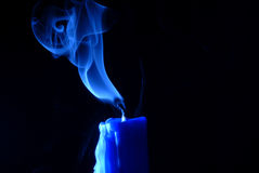 Blue Candle. Closeup of the top section of a taper candle recently extinguished, with smoke rising from the wick. Isolated on black background stock photography