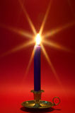 Blue candle in brass holder on red. Royalty Free Stock Photography
