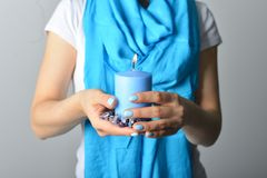 Blue candle in hands royalty free stock photos