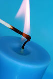 Blue candle with match Stock Photography