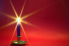 Blue candle on red background. Stock Photography
