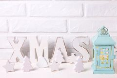 Blue candleholder, word Xmas made from wooden letters, wooden stars, hearts and trees, fairy lights near by white brick wall. Place for text. Selective focus royalty free stock photography