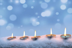 Blue candles burn in the snow Royalty Free Stock Photo