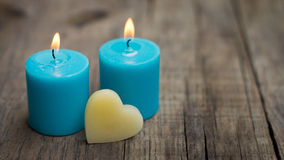 Blue Candles. Blue burning candles with a heart on wood background royalty free stock photos