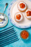 Blue candles, a plate with donuts and jam on a turquoise table close-up. Vertical Stock Image