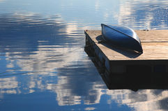 Blue Canoe. Resting on dock beside still blue water reflecting the clouds and blue sky Stock Images