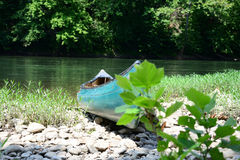 Blue canoe beached on river bank Royalty Free Stock Image