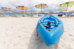 Blue canoe with colorful beachbeds Royalty Free Stock Photos
