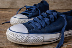 Blue canvas shoes on wooden background with copy space. Stock Images