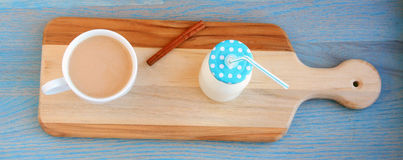 Blue cap cinnamon stick jug of milk next a and mug of coffee Royalty Free Stock Photo