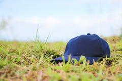 Blue cap put on grass field Stock Photography