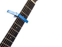 Blue capo on guitar fingerboard, white background Royalty Free Stock Photo
