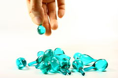 Blue capsule and hand in isolate Royalty Free Stock Photos