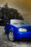 Blue car. A filtered car portrait of a blue passenger vehicle in front of forest Stock Photos