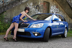 The blue car. A young woman has a suitable minidress to the car Stock Photos