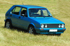 Blue car. A blue middleclass new small dirty car (VW Citi Golf, South Africa) standing parked in the grass on a meadow in sunshine outdoors Stock Photos