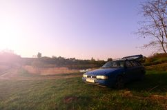 A blue car on a background of a rustic landscape with a wild cane field and a small lake. The family came to rest on the nature n Royalty Free Stock Images