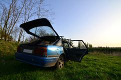 A blue car on a background of a rustic landscape with a wild cane field and a small lake. The family came to rest on the nature n Stock Photos