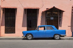 Blue car in Cuba. Vintage car in front of a pink colonial house in Cuba stock photography