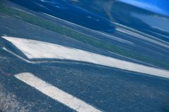 Blue Car Door Reflecting Parking Lot. Bizarre, abstract, impressionistic image of a parking lot are reflected in blue car door in the daytime around noon in June Royalty Free Stock Images